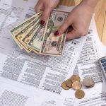 Mujer contando dinero sobre declaraciones de impuestos. Concepto: ¿Qué son los ingresos no sujetos a impuestos?