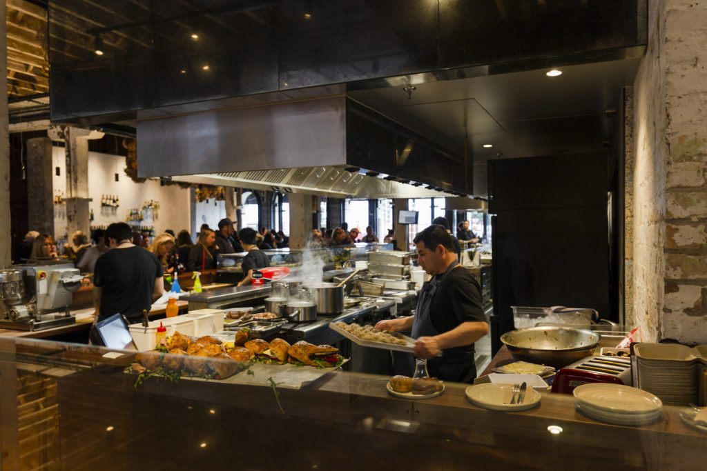 Busy and profitable restaurant with open-concept kitchen. Concept: profit margin in restaurants.