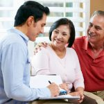 Financial Advisor Talking To Senior Couple At Home Writing Documents Smiling. Concept: Business Loan Fees