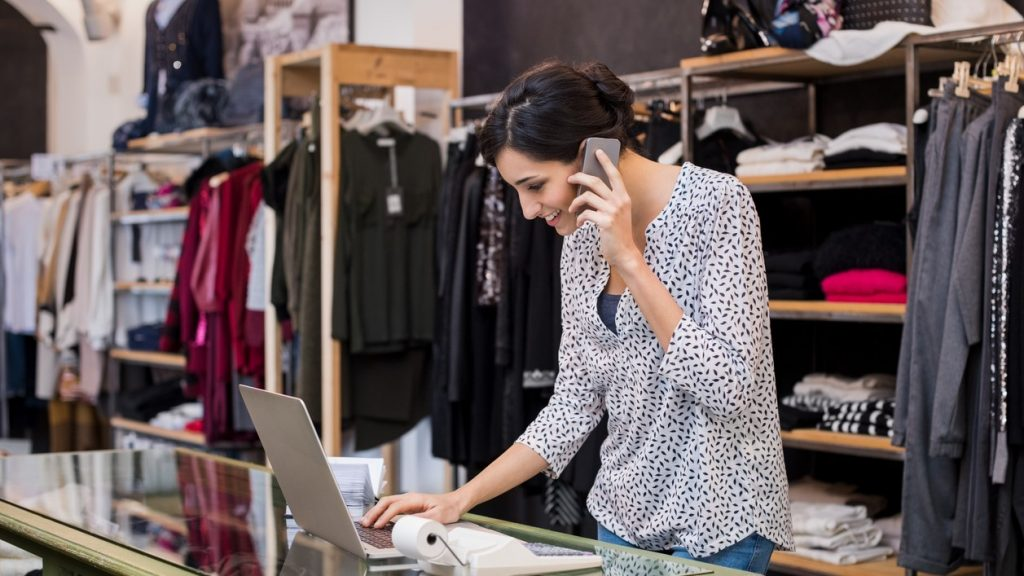 Young businesswoman talking over phone while checking laptop in her clothing store. Young entrepreneur in casual using laptop and talking on mobile. Store manager woman checking important documents on laptop. Small business concept. Concept: business loan fees