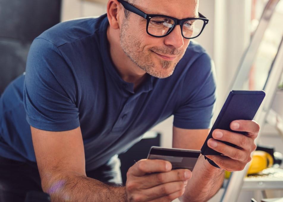 Hombre comprando manerial de contrucción en línea en su celular mientras trabaja. Concept: tarjeta de crédito, gastos empresariales