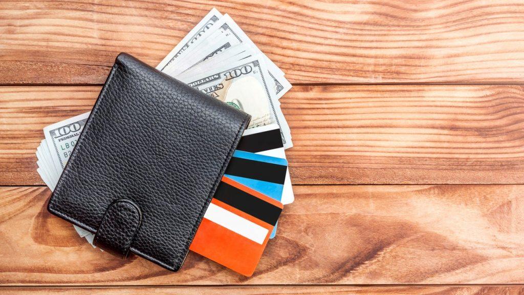 Cartera, billetes y tarjetas de crédito en una mesa de madera. Concept: tarjeta de crédito, gastos empresariales