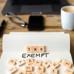 Closeup on notebook over desk, front focus on wooden blocks with letters making Tax Exempt text. Concept: what is a tax exemption.