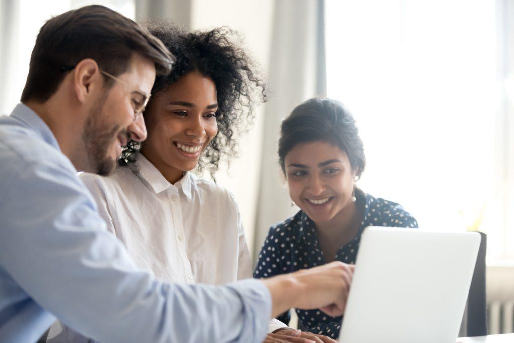 Trabajadores diversos en una oficina revisando una computadora. Concept: software de facturación