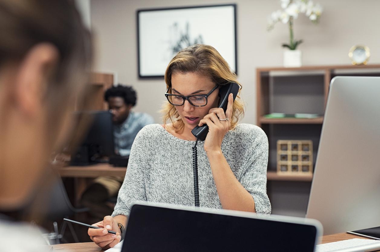 Female employee talking on phone in office. Concept: landline plans vs cell phone plans