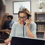 Empleada hablando por teléfono fijo en oficina. Concepto: Planes de telefonía fijos o planes de telefonía móvil