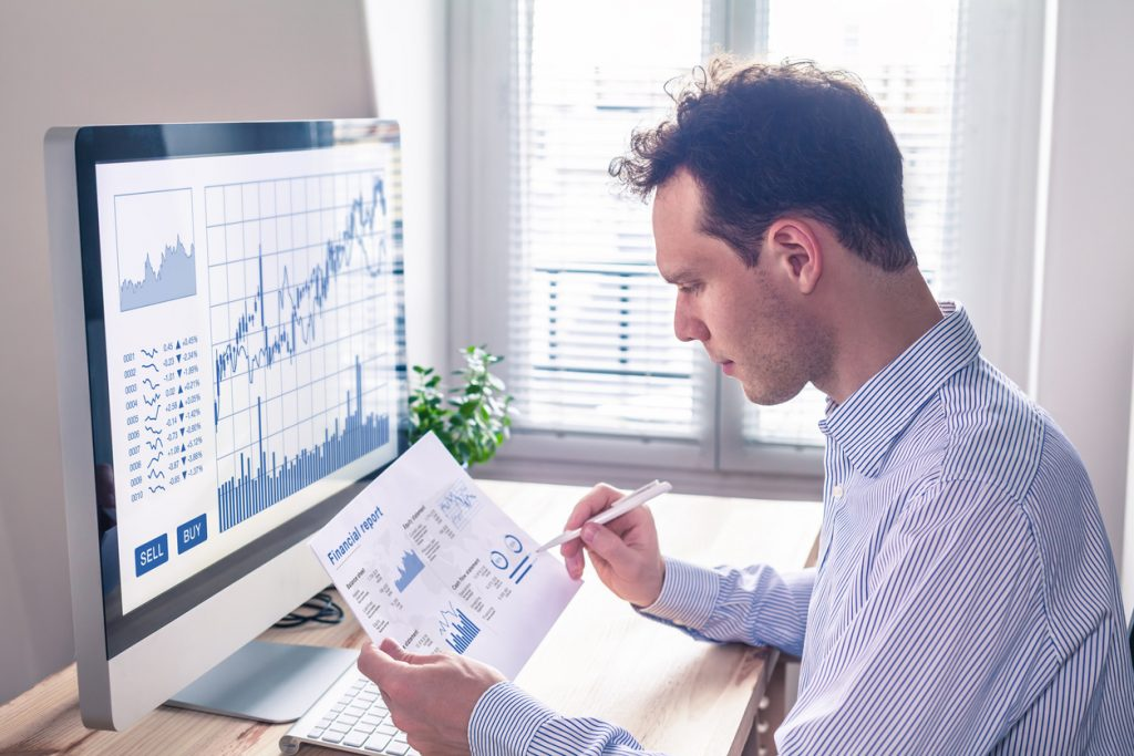 Trader analyzing financial report and trading charts and computer screen for successful sell buy strategy of stock market investment.