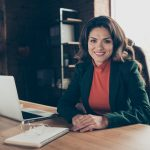 Foto de una empresaria sentada en su oficina trabajando frente a un cuaderno y una laptop. Concept: software de impuestos