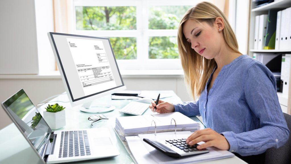 Mujer de negocios calculando cuentas con laptop, computadora de escritorio, calculadora y cuaderno. Concept: software de impuestos