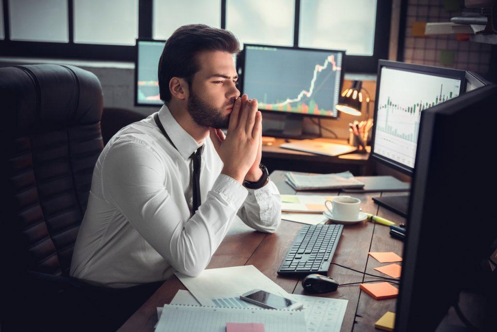 Man trader at office sitting at table looking at monitors wondering options vs stocks?