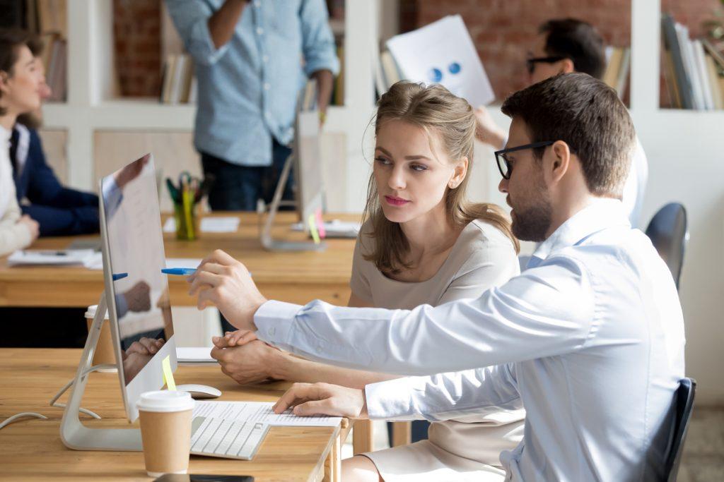 Empleados trabajando frente a computadora en oficina. Jefe enseñando a empleada como usar un programa de computadora. Concept: Descuentos de software de impuestos