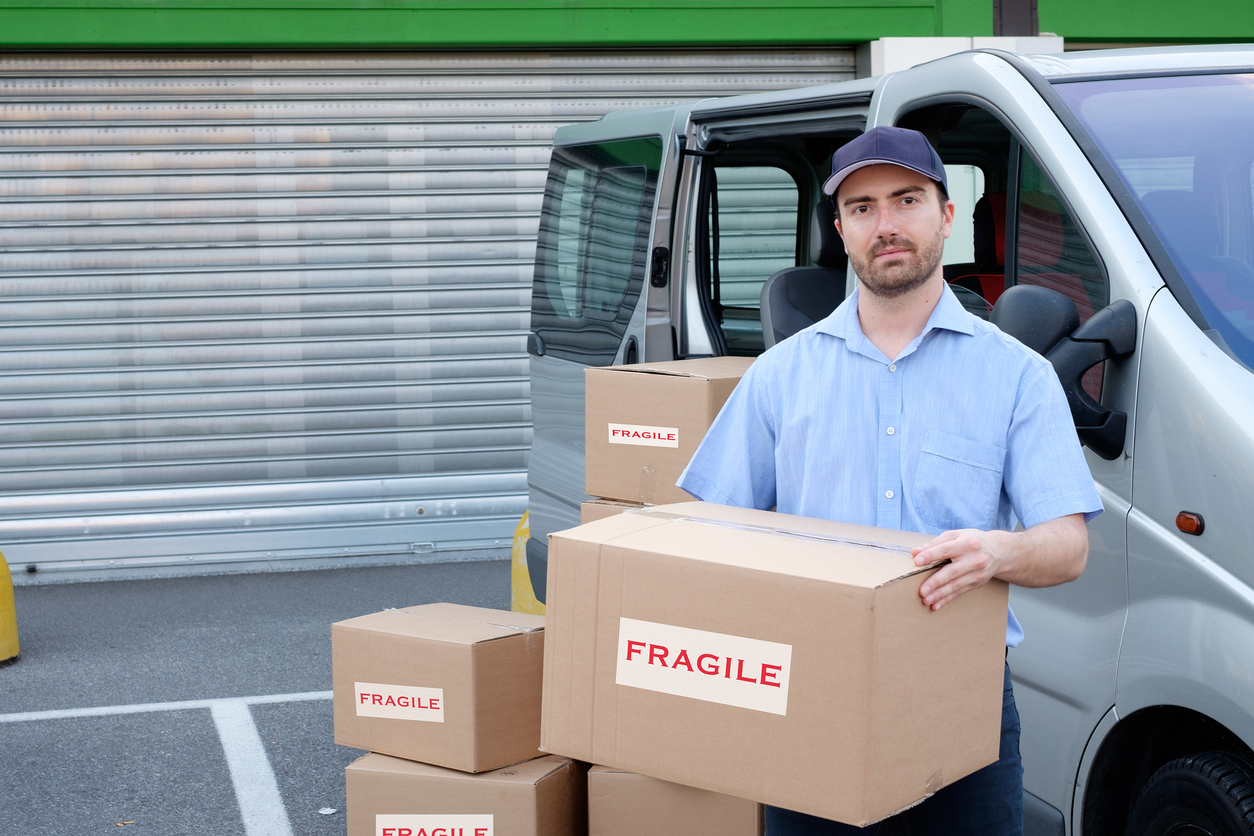 Express courier next to his delivery van. Concept: Commercial car insurance ve personal car insurance.