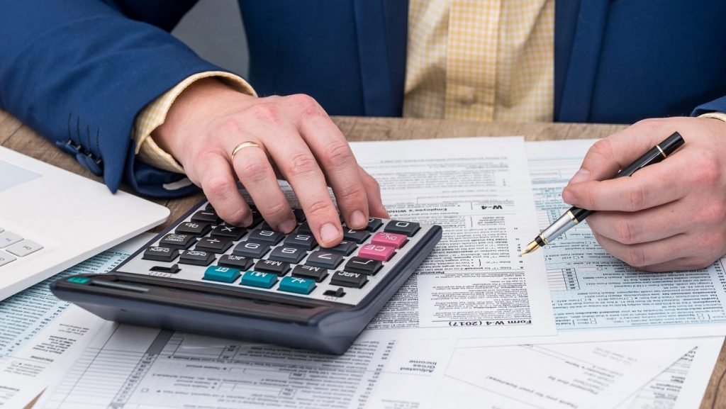Businessman works with W-4 tax form and calculator. cocnept: quarterly taxes