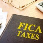 Impuestos FICA y calculadora en una mesa. Concept: Qué son los impuestos FICA