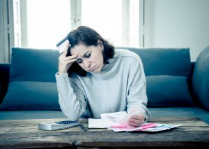 Young attractive woman looking stressed and worried with card payments and home finances accounting costs charges taxes and mortgage in paying bills financial problems and credit card debts concept. concept: business loan