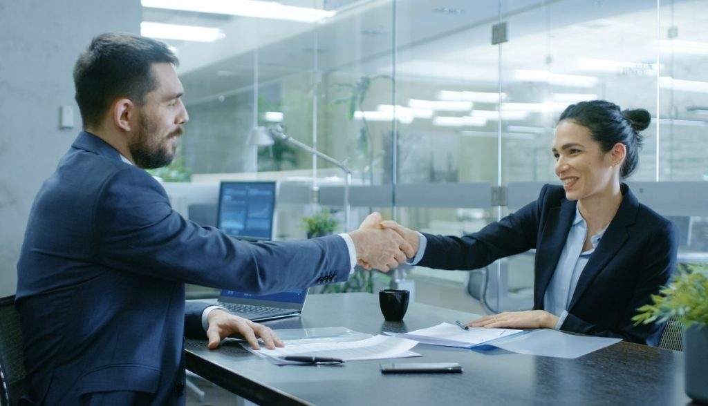 Businesswoman and Businessman Shake Hands. Draw up a Contract, Filling Papers in Conference Room. In the Background Modern Bright Office with Glass Walls. Concept: business loan