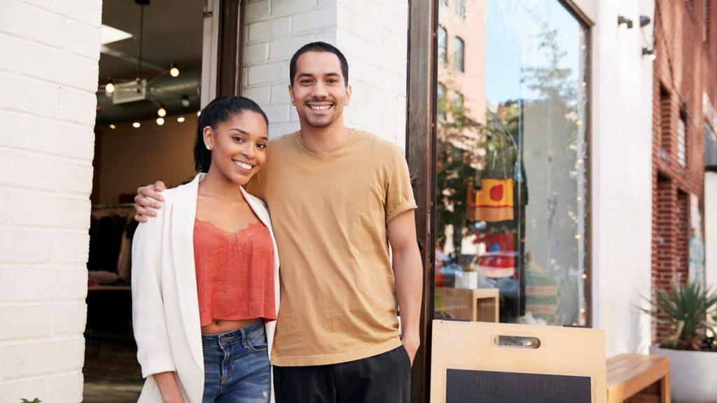 Pareja latina afuera de su tienda sonriendo. Concept: Impuestos trimestrales e impuestos anuales