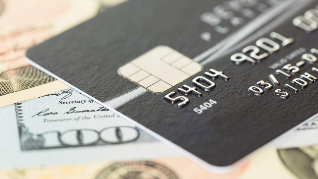 Black credit card on dollar banknote. concept: pay mortgage with credit card