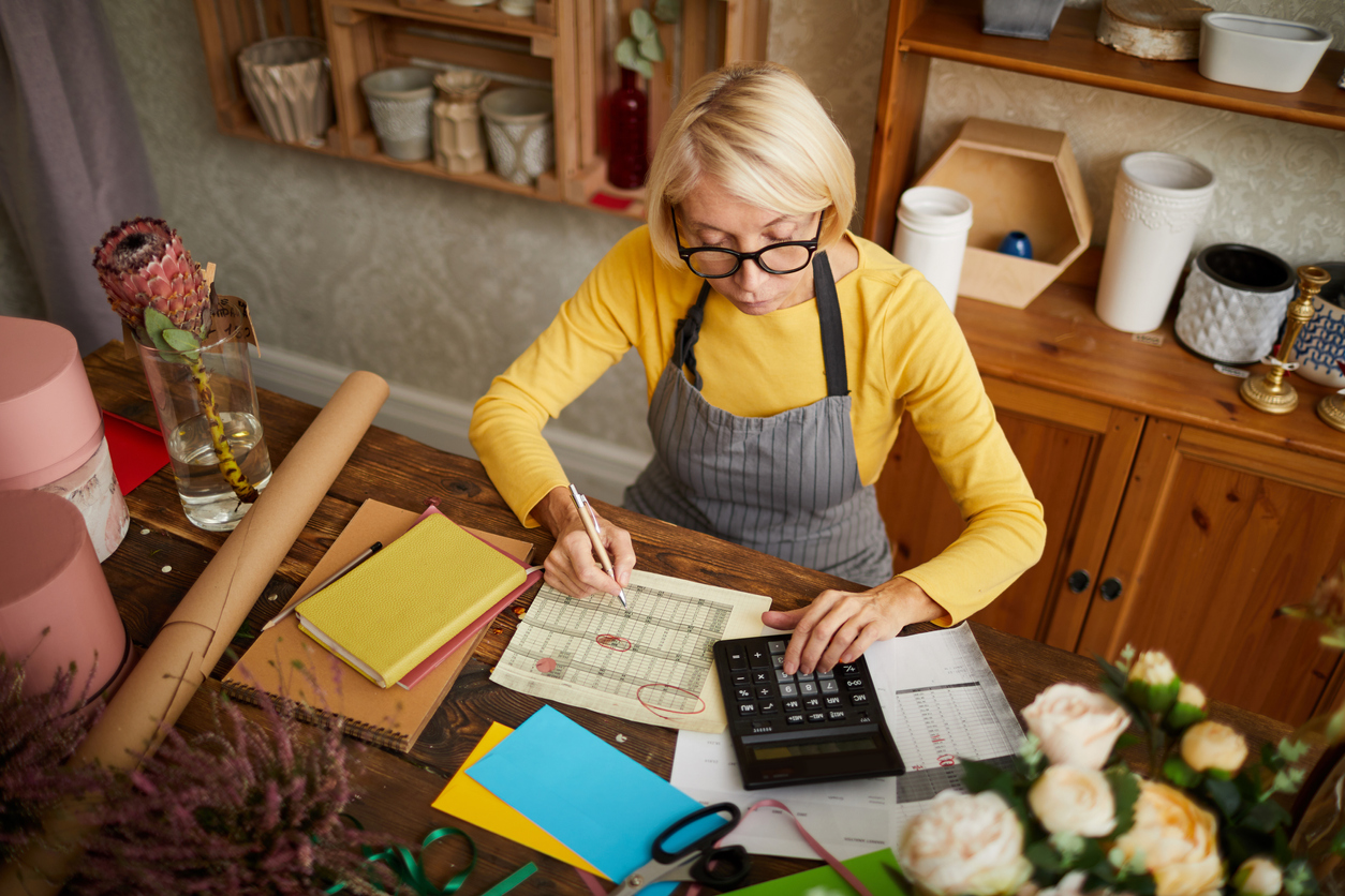High angle portrait of female businesswoman counting finances using calculator in small shop, copy space. Concept: quarterly taxes