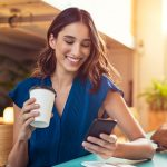 Young beautiful woman holding coffee paper cup and looking at smartphone while sitting at cafeteria. Happy university student using mobile phone. Businesswoman in casual clothes drinking coffee, smiling and using smartphone indoor. concept: best cell phone plans