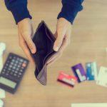 Manos abriendo una cartera vacía encima de una calculadora y tarjetas de crédito, deuda. Concept: