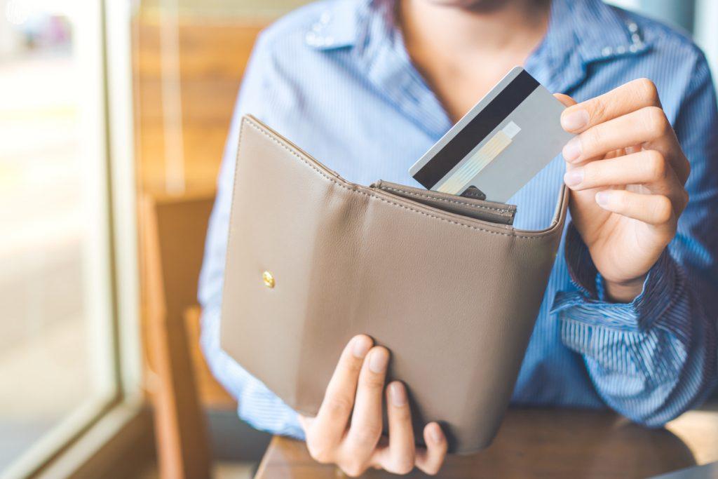 Mano de mujer sacando una de las mejores tarjetas de crédito aseguradas de su cartera