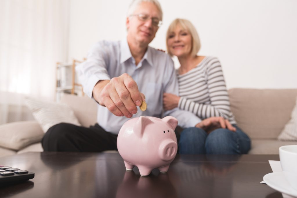 Senior couple putting coin in piggybank, saving money at home. Concept: What are annuities?