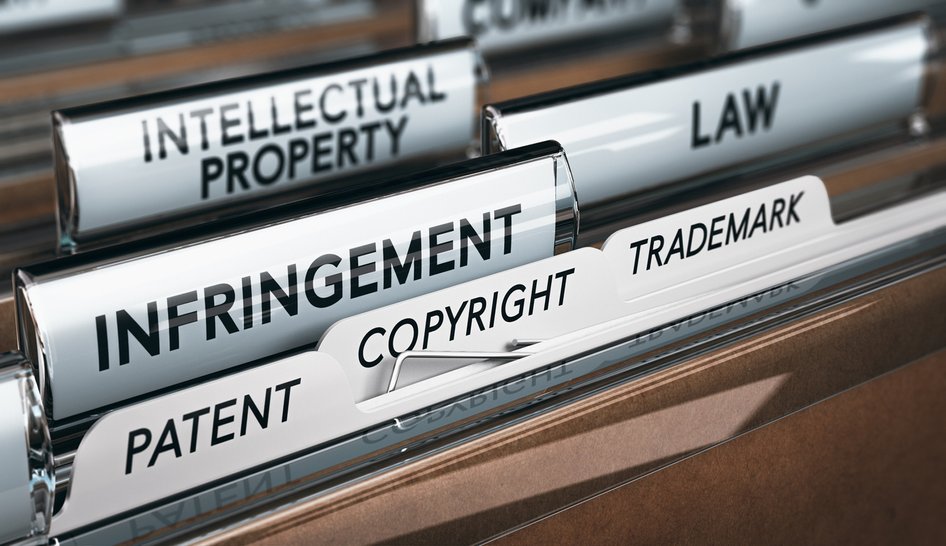 3D illustration of a folder, focus on a tab with the word infringement. Conceptual image of copyright law. Concept: Copyright vs Trademark vs Patent