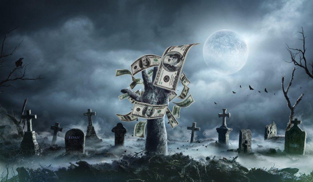 Mano de un muerto viviente saliendo de la tumba en cementerio con niebla y billetes. Concept: deuda zombie