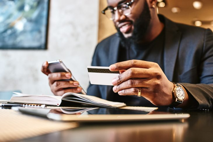 Portrait of African-American male holding cell phone in one hand and unsecured credit card in other, making transaction, using mobile banking app during lunch at cafe. Concept: what is an unsecured credit card?