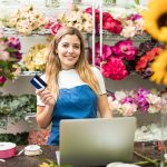 Flower shop owner holding a credit card next to a laptop computer in her flower shop. Concept: best unsecured credit cards.