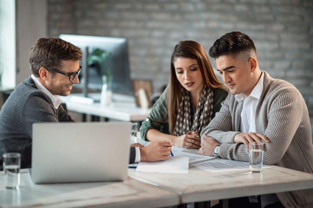 Pareja joven con asesor financiero leyendo reportes financieros en una oficina. Concept: ¿Qué hace un asesor financiero?