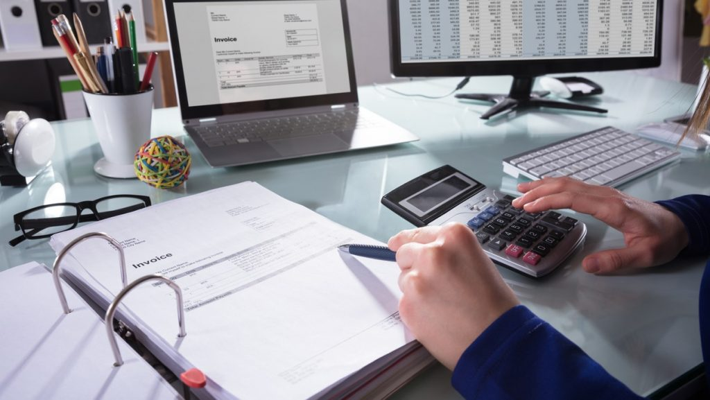 Close-up Of A Businessperson's Hand Calculating Invoice At WorkplaceConcept: What Does a Financial Advisor Do