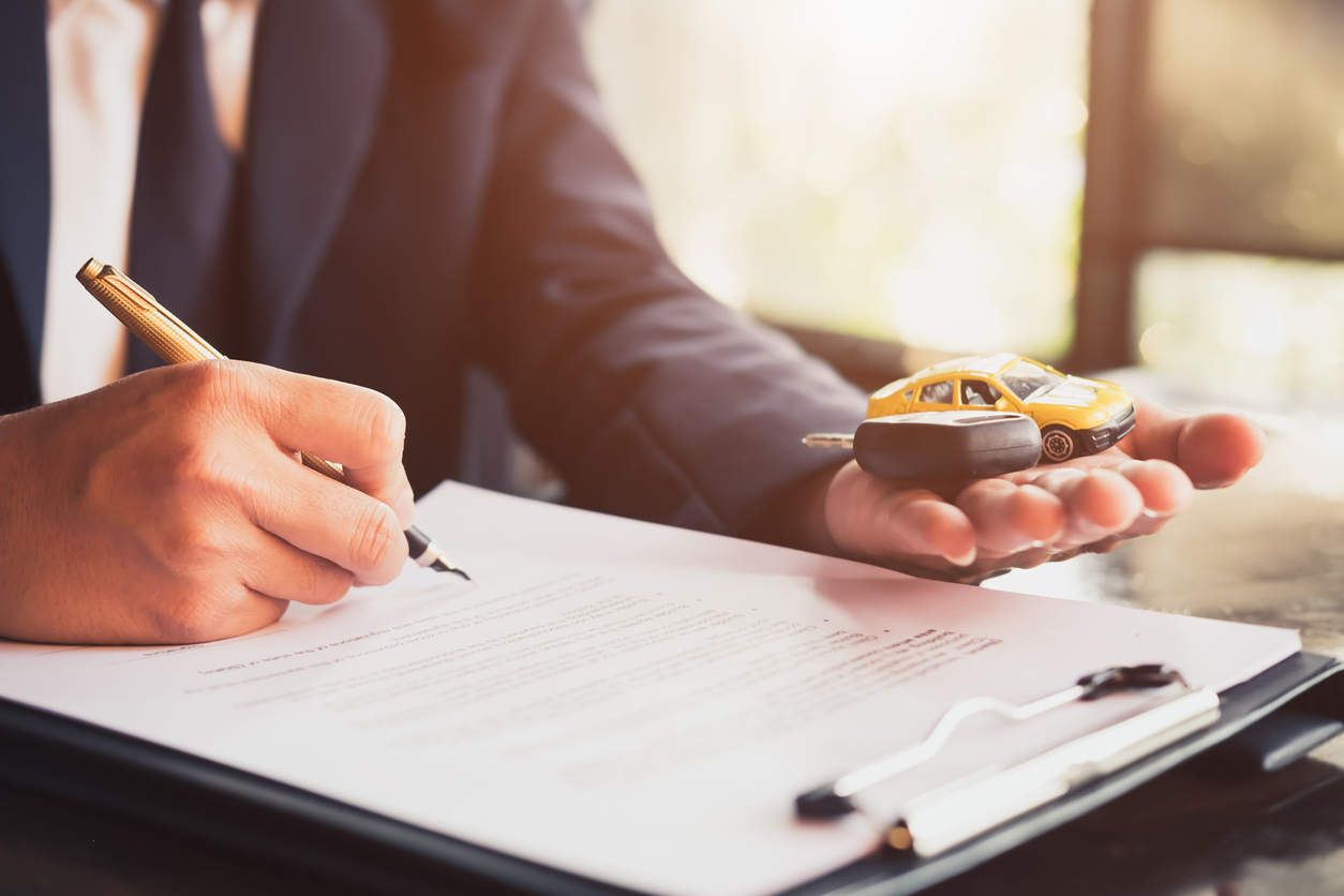 Close up business man reaching out sheet with contract agreement proposing to sign.Insurance agent and insurance company customers.Concept of insurance with house and car. Concept: Can You Refinance A Car Loan?