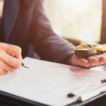 Close-up de un hombre de negocios firmando contrato de préstamo de su automóvil comercial Concept: ¿Se puede refinanciar un préstamo automovilístico?