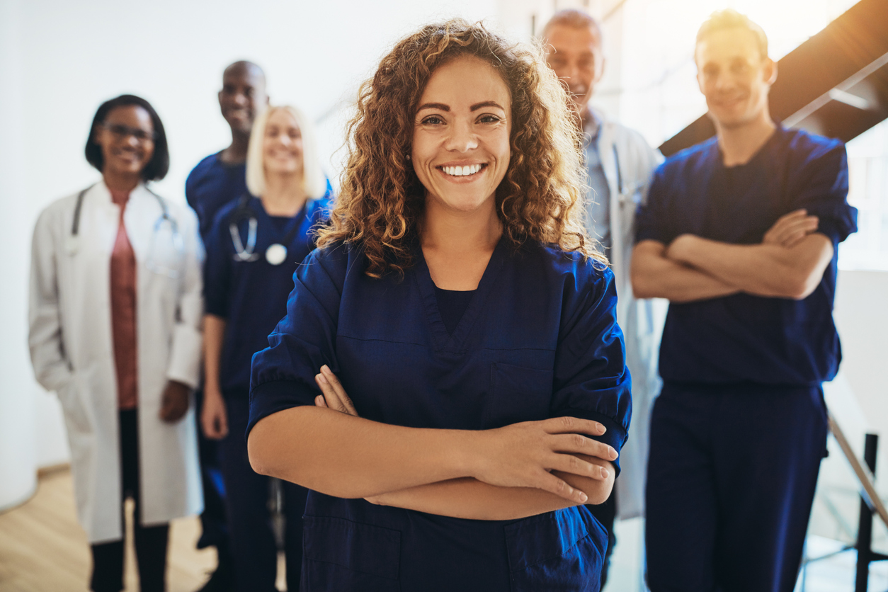 Young female doctor smiling while standing in a hospital corridor with a diverse group of staff in the background. Concept: how to choose health insurance