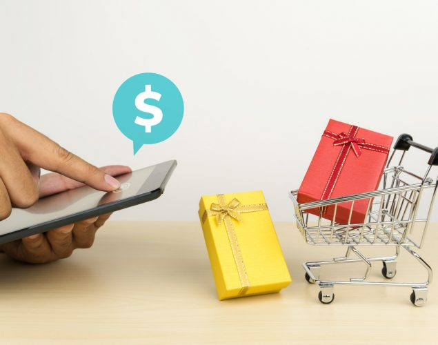 hand holding a digital tablet and press the button to shopping online, a red gift box in a shopping cart and a yellow gift box on the table. Concept: What is discretionary income?