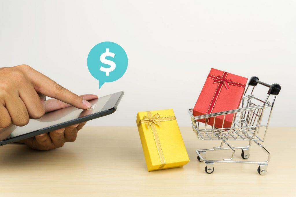 Mano usando calculadora y carrito de la compra con regalos en miniatura. Concepto: ¿Qué son los ingresos discrecionales?