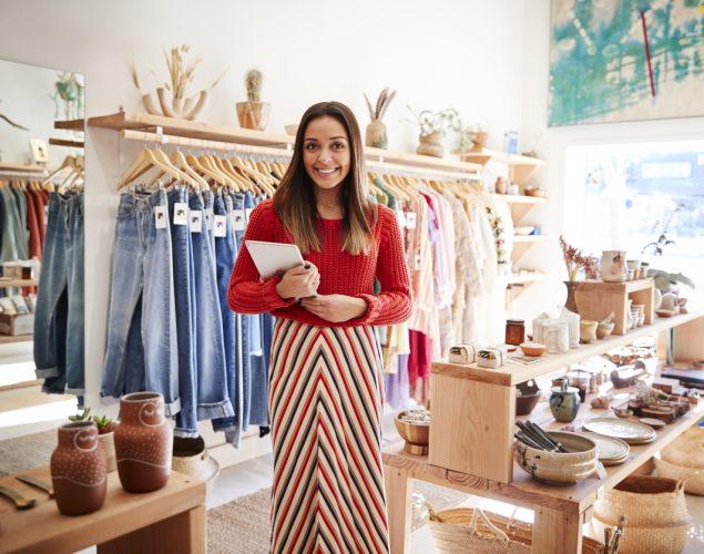 Retrato de una mujer de ne3gocios en su tienda de ropa con tablet. concept: negocio de ropa