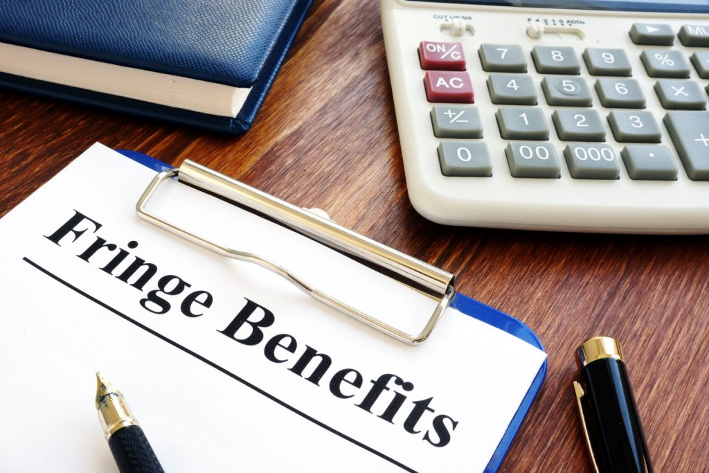 Fringe Benefits documents with clipboard and calculator. Concept: fringe benefit