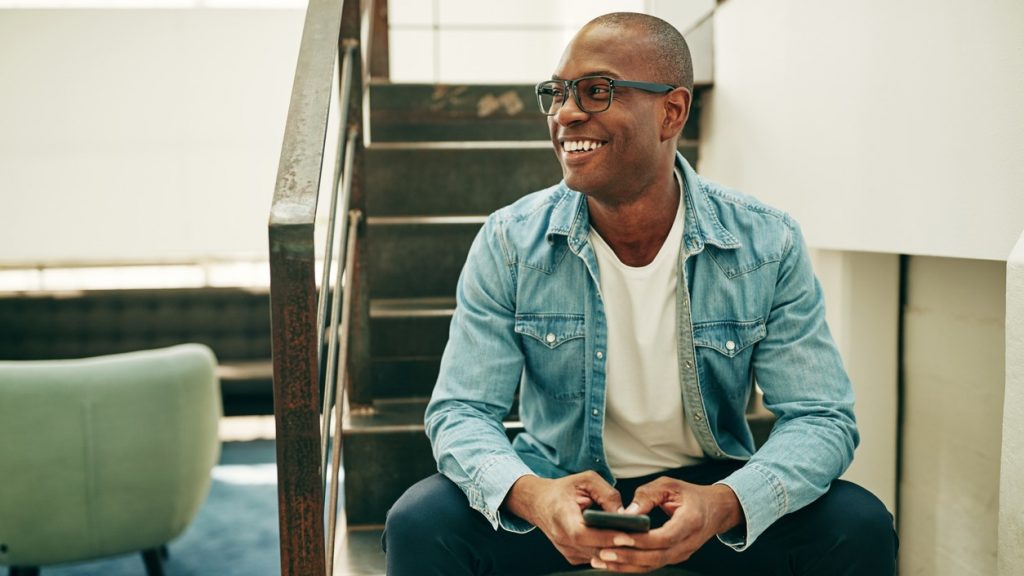 Smiling young African businessman wearing glasses and reading text messages on a cellphone while sitting on stairs in an office. concept: fringe benefit