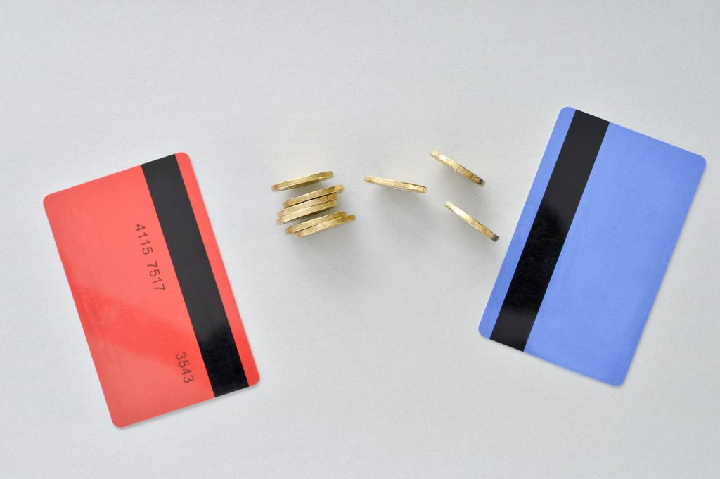 Bank cards are in the colors of living coral and blue with shiny yellow coins symbolizing the electronic exchange of money. Concept: What is Balance Transfer?