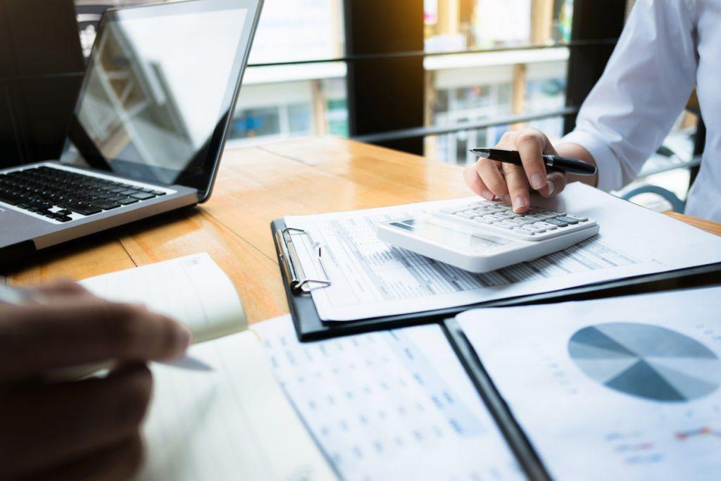 Auditoría en un negocio, personas usando calculadora, datos financieros, inversiones. Concept: seguimiento de gastos comerciales