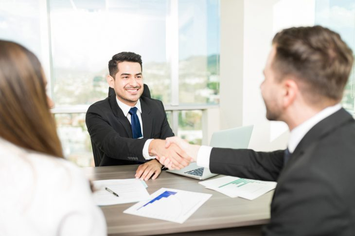 Financial adviser sealing a deal with clients at desk in office. Concept: open a bank account