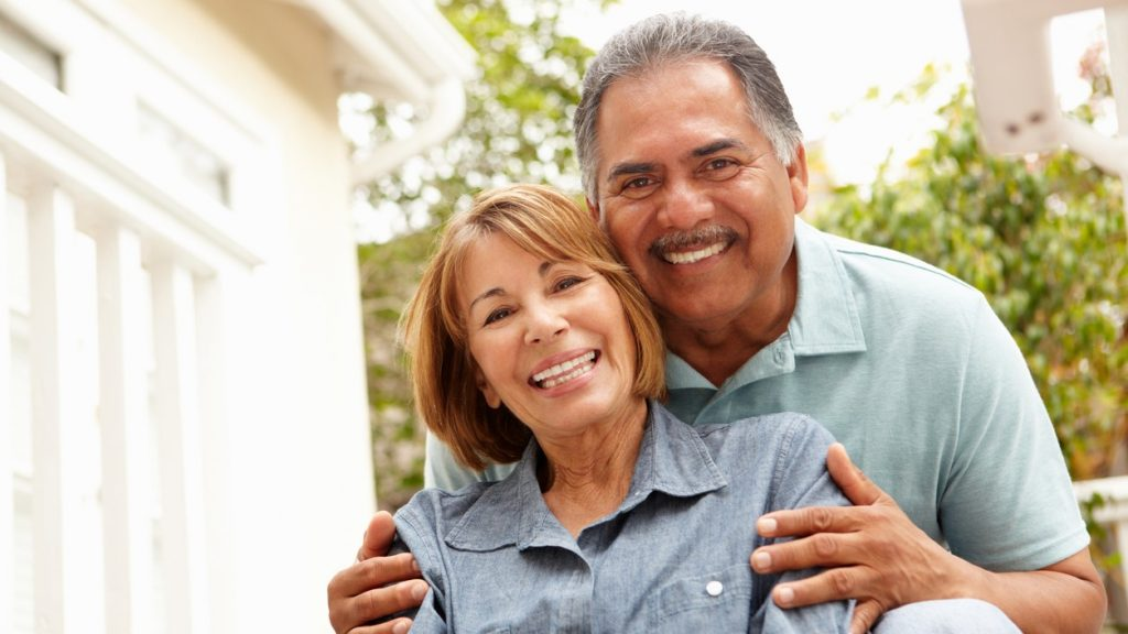 A close-up of a smiling senior couple. The man and woman are wearing light blue shirts and are seated. The woman is in front of the man, and the man's hands are embracing her shoulders. Out-of-focus bushes are visible in the background. concept: open a bank account