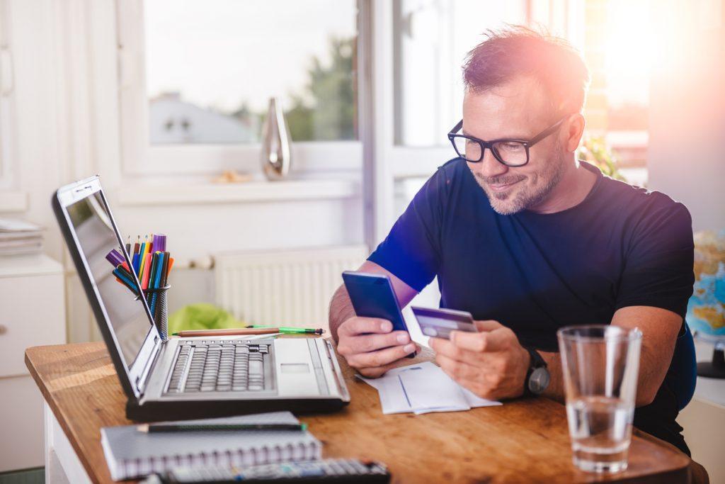 Hombre en escritorio usando tarjeta de crédito y smartphone. Concepto: Cómo elegir una tarjeta de crédito