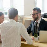 Abogado o consultor financiero amigable consultando con una pareja joven. Concept: seguro contra interrupción de actividades comerciales