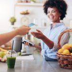 Dueña de negocio de jugos recibiendo pago de tarjeta de crédito de un cliente. Concepto: ¿Qué es el APR en una tarjeta de crédito?