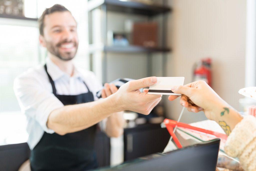 Manos de un cliente pagando a vendedor con una tarjeta de crédito en una panadería. concept: tarjeta prepagada