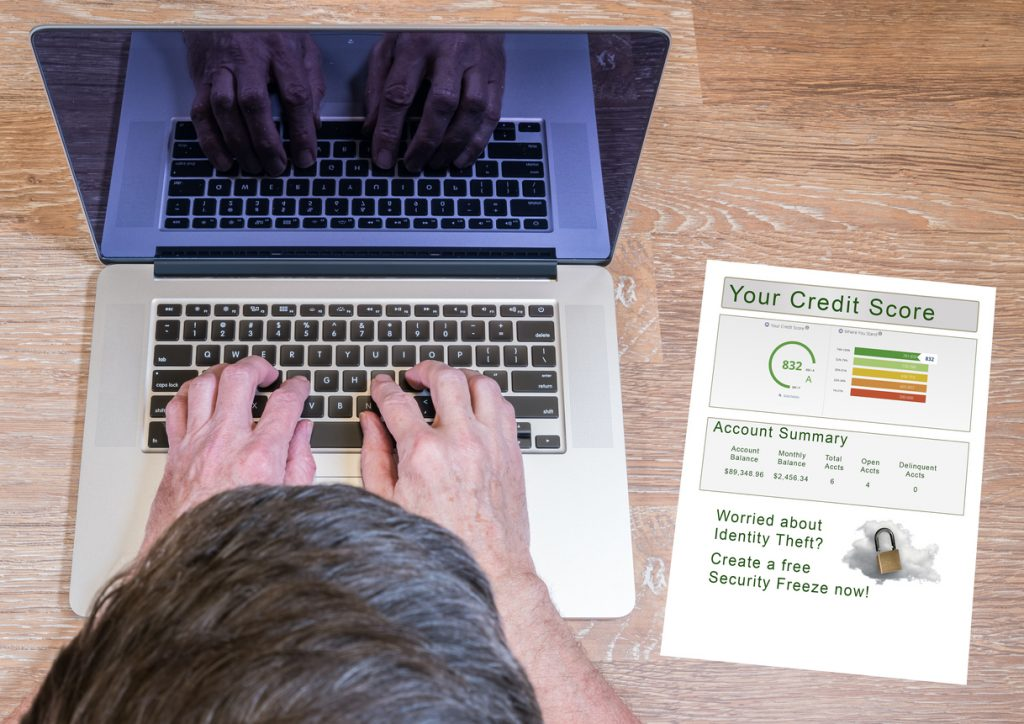 Senior man typing on laptop with a credit report and credit freeze option on desk. concept: 3 credit bureaus